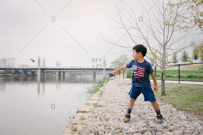 Young boy throwing rock into river