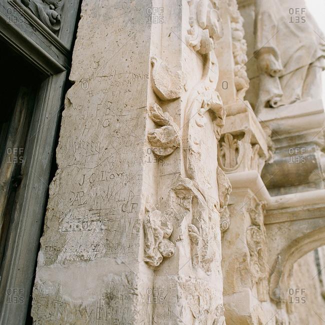 Historic graffiti carved into limestone at Mission San Jose in Texas