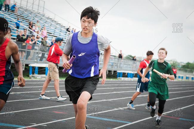 Boy running baton track race