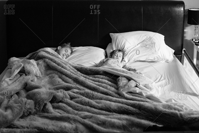 Kids asleep in cozy bed