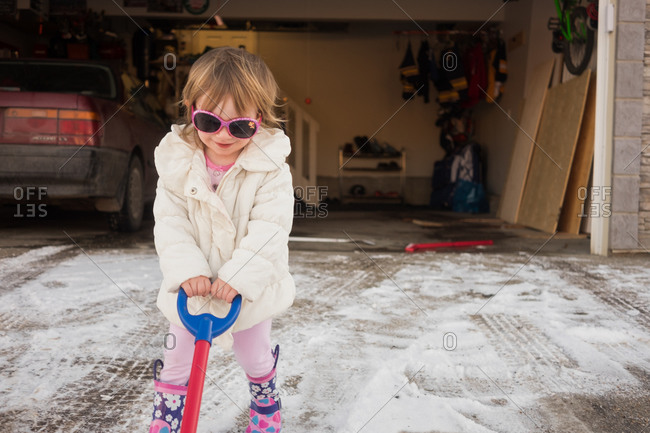 Girl playing with snow shovel