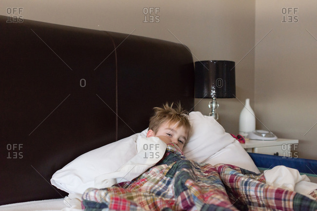 Sleepy boy under covers