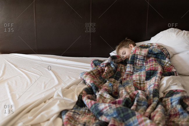 Boy asleep under blankets