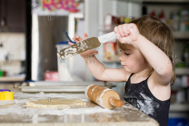 Girl with spatula making cookies