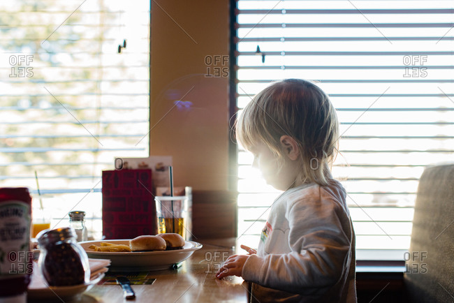 Girl in sunlight in diner