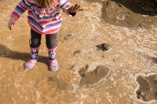Girl standing in a mud puddle