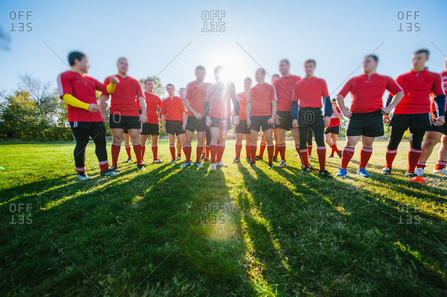 Rugby Union players standing in line on football field, preparing for the game with sun behind them and big shadows on the green field with focus on legs