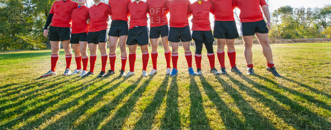 Rugby players together in line preparing to make a huddle with focus on legs and shadows