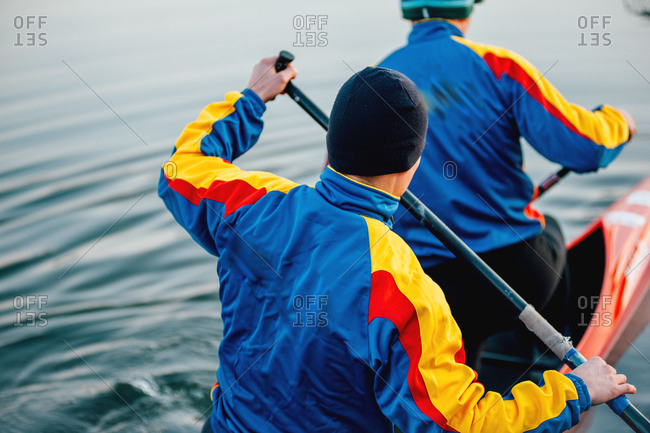 Team of two young men of a competitive sprint canoe team practice for an upcoming competition on a cold morning