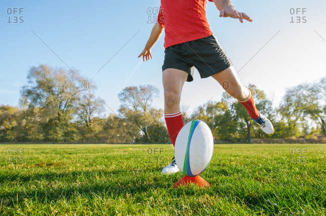 Powerful man kicking the ball for a goal on rugby field