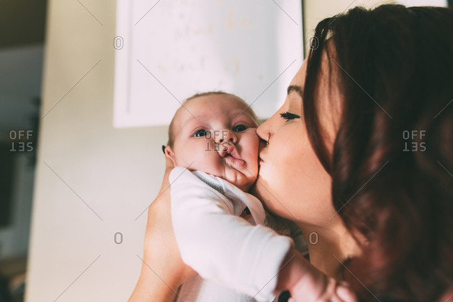 Mom giving infant a kiss