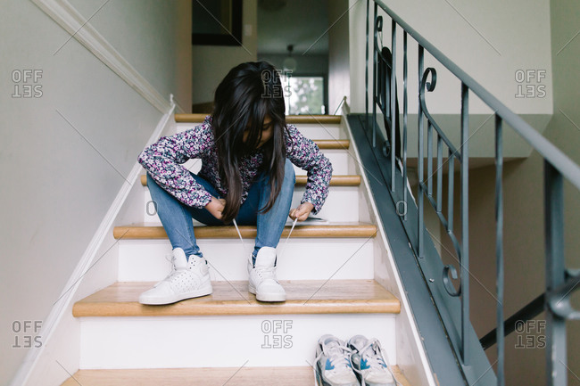 Girl on steps tying her shoes