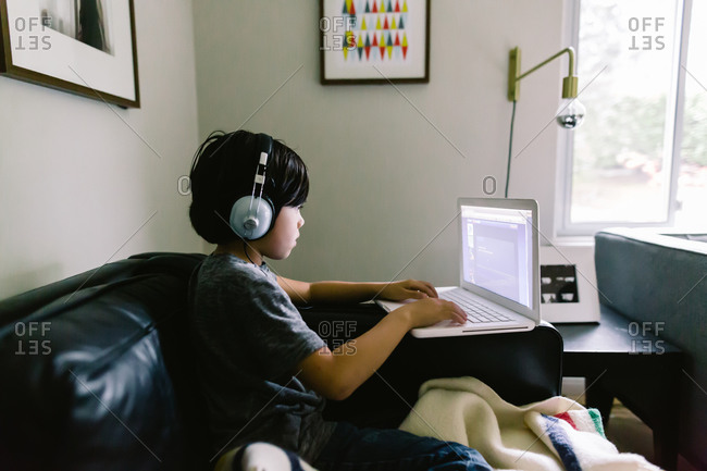 Boy listening to a laptop