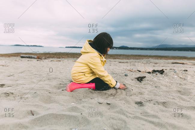 Girl in rain boots on beach