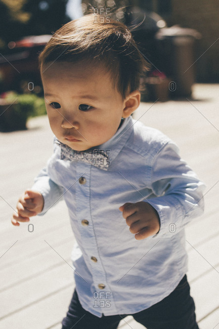 Toddler boy in a button-up shirt and bowtie
