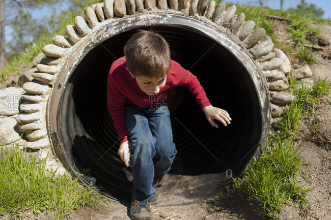 Boy emerging from drain