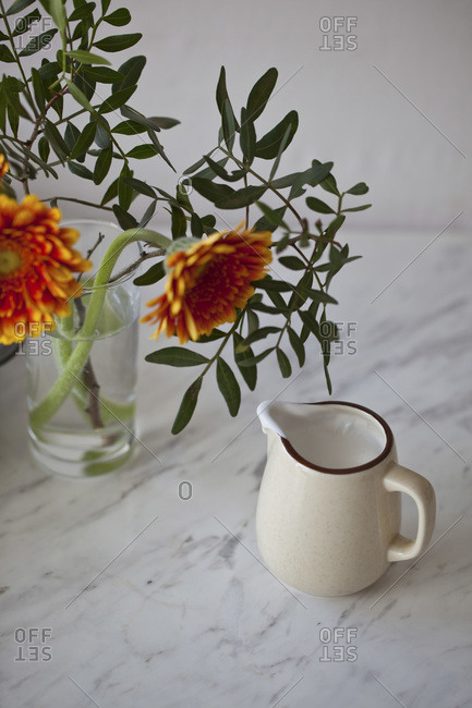 Orange flowers and pitcher of coconut cream on a white marble table