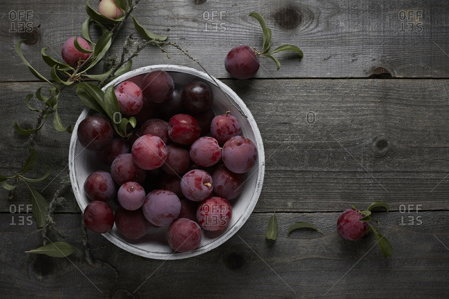 Fresh picked plums spilling from a white ceramic bowl