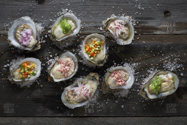 Oysters on the half shell topped with an assortment of colorful sauces