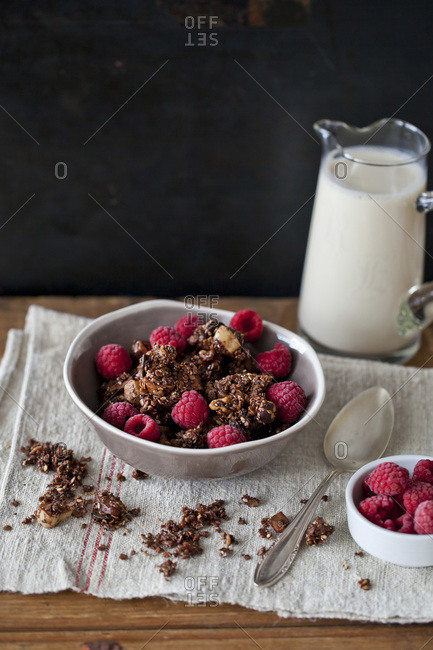 Homemade chocolate granola with raspberries and a pitcher of soy milk
