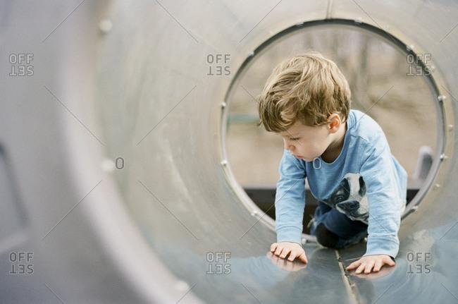 Boy climbing in play tube