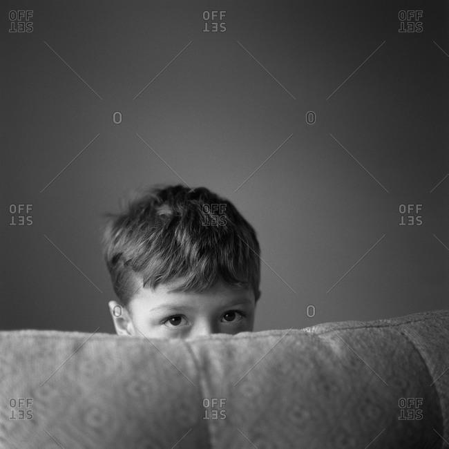 Boy peeking over sofa