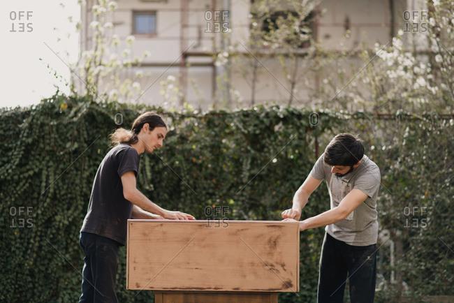 Two men sanding a dresser