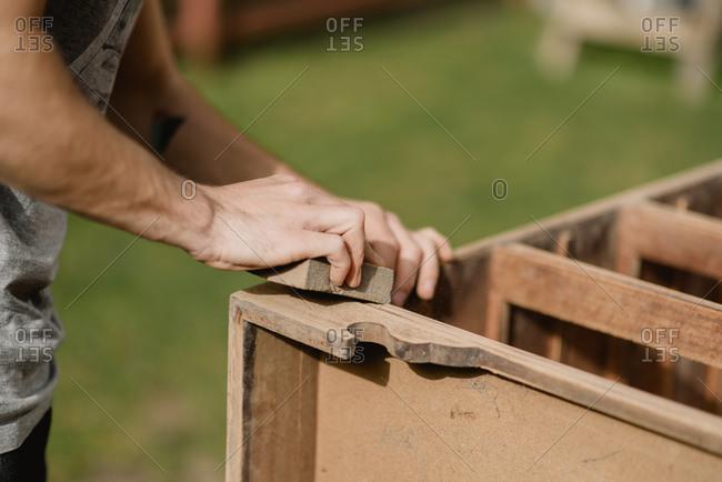 Man sanding down dresser