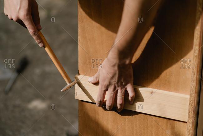 Hands repairing a dresser