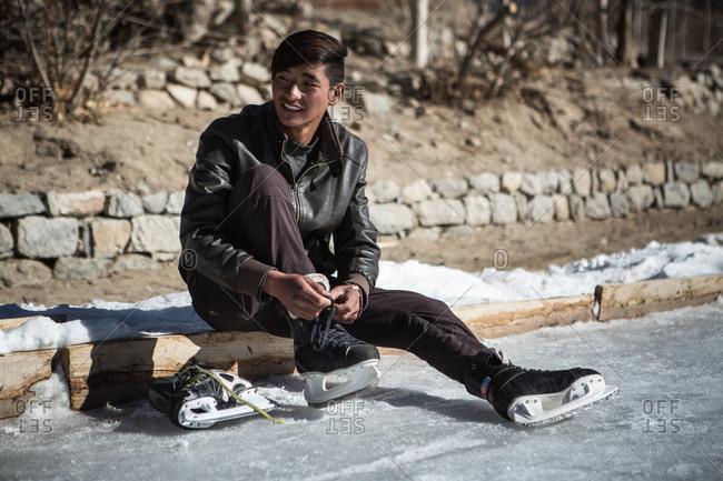 Leh, India - February 12, 2015: Teen boy putting on skates