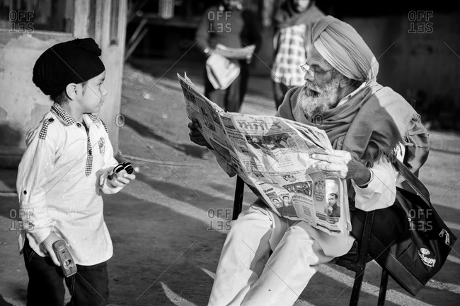 Amritsar, India - March 18, 2015: Boy watching man with newspaper
