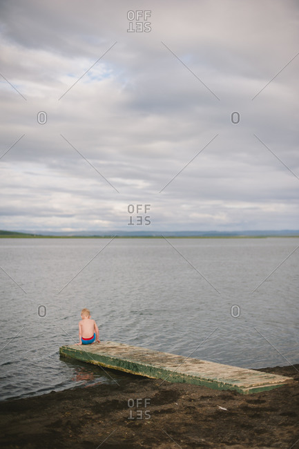 Boy sitting at the end of the dock at a lake in Iceland
