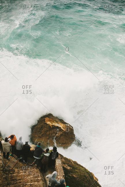 People watching waves crashing against the rocks