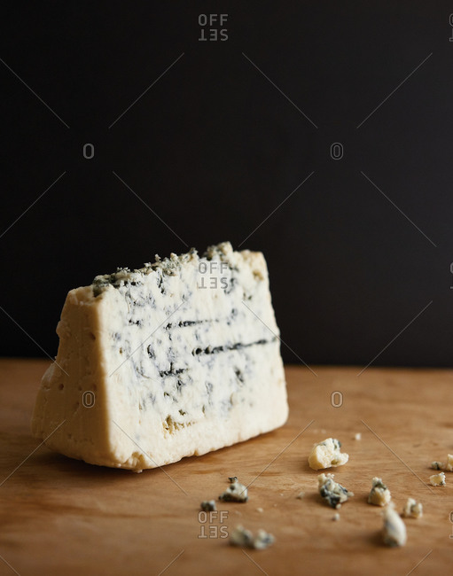 Blue cheese wedge on wood surface