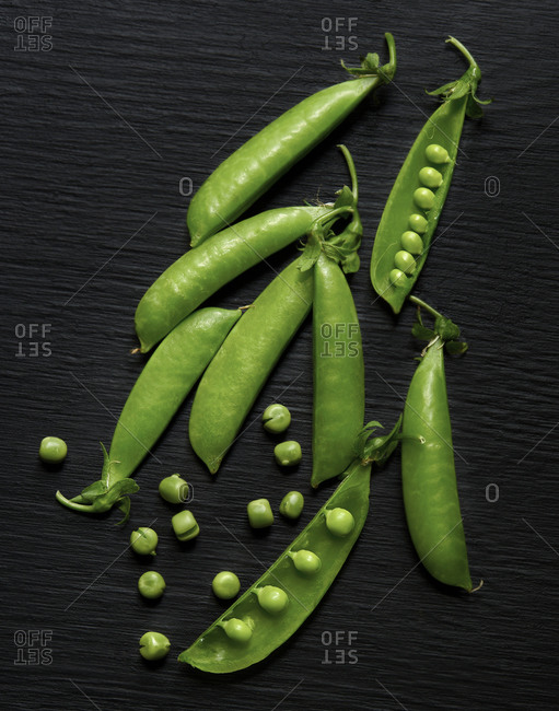 Closed and opend pea pods on a dark surface
