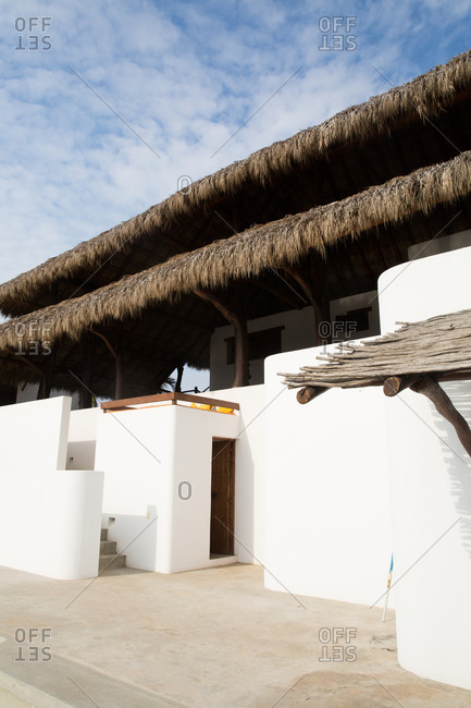 White stucco building with palm thatch roof