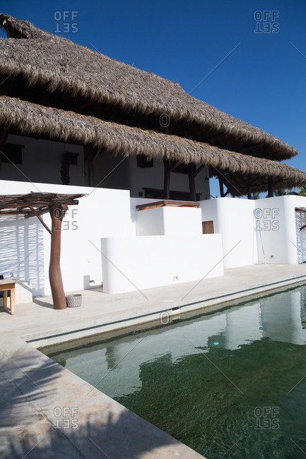 Pool at a luxurious vacation home with thatched roof