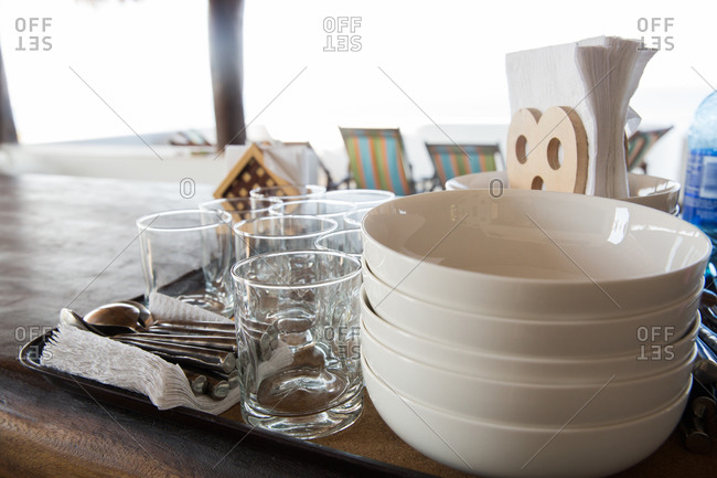 Close-up of tray of bowls and glassware on wooden table
