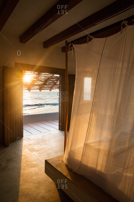 Sunset through bedroom door of tropical home in Mexico