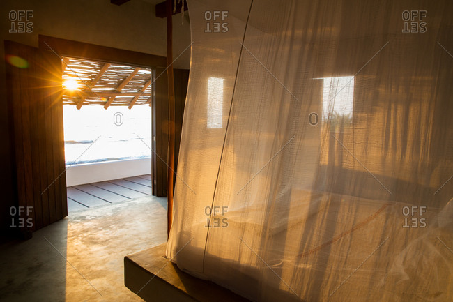 Sunlight shining through curtains around bed