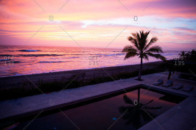 Beautiful pink sunset over oceanfront pool