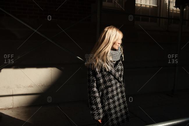 Woman under scaffolding in sunlight