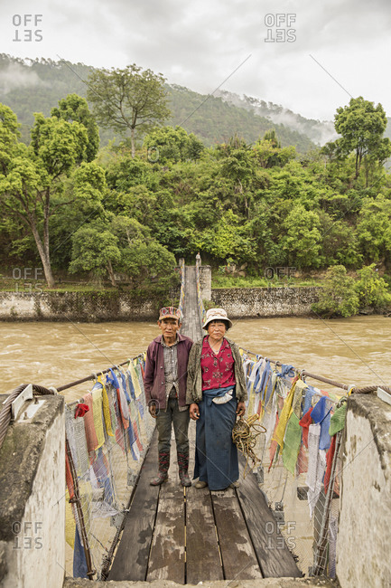 Bhutan - May 20, 2015: Local farmers on a bridge lined with traditional Buddhist prayer flags in Punakha valley, Bhutan