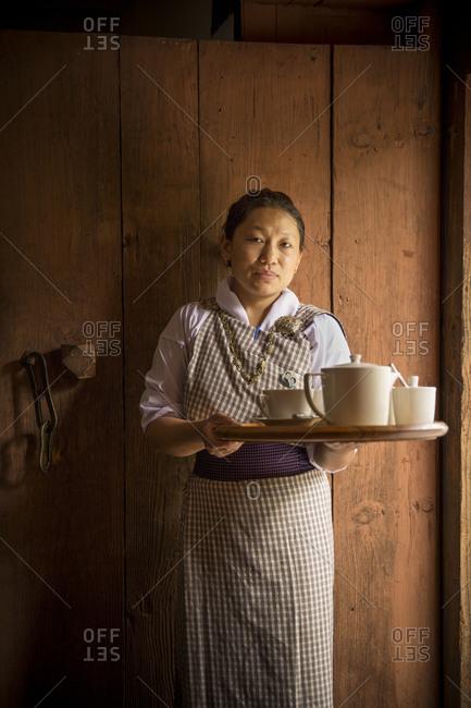 Bhutan - May 20, 2015: A local waitress serving Bhutanese tea in Punakha valley, Bhutan