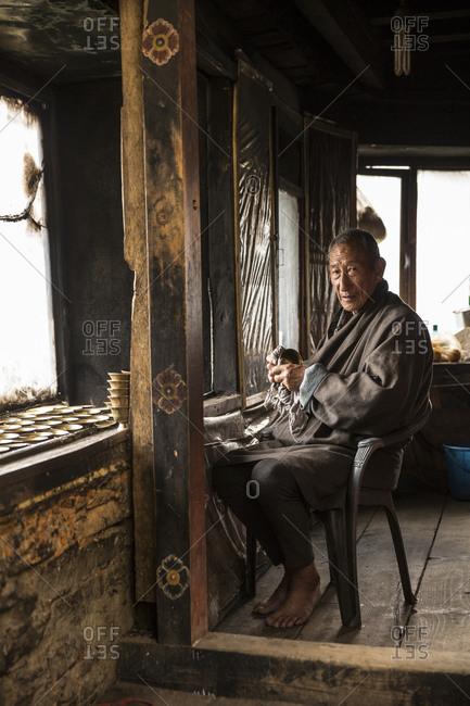 Bhutan - May 21, 2015: A local preparing prayer candles near the Tiger's Nest Monastery, Bhutan