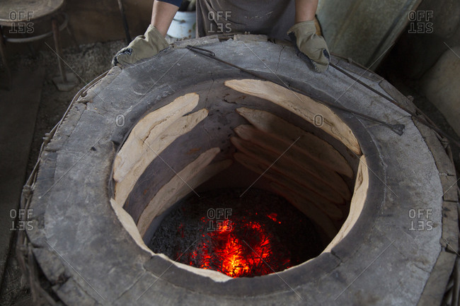 Traditional sourdough bread being baked in a wood fired pit, Signaghi, Georgia