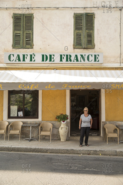 Corsica, France - June 17, 2014: A French woman standing outside a cafe on the island of Corsica