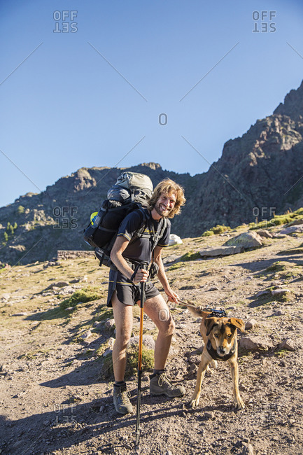 Corsica, France - June 17, 2014: Man hiking with his dog along the GR20 trail on the island of Corsica