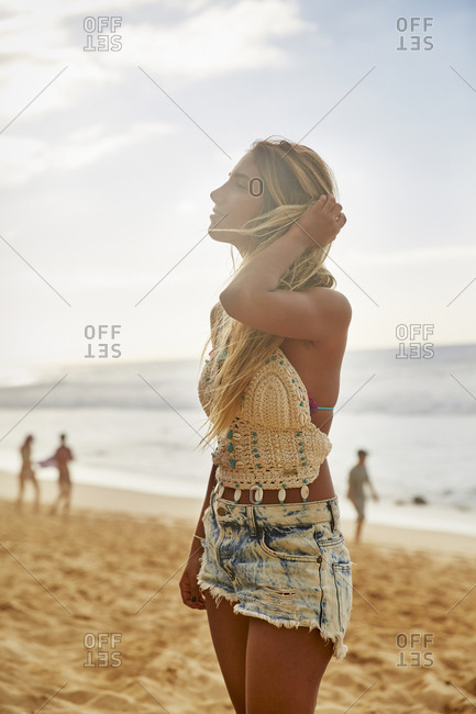 Hawaii - February 1, 2015: Woman wearing denim shorts and halter top on a beach on the North Shore of Oahu