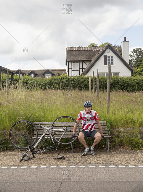 Denmark - June 15, 2015: A biker stopped for repairs in front of a thatched house along a road in Strandvejen, Denmark